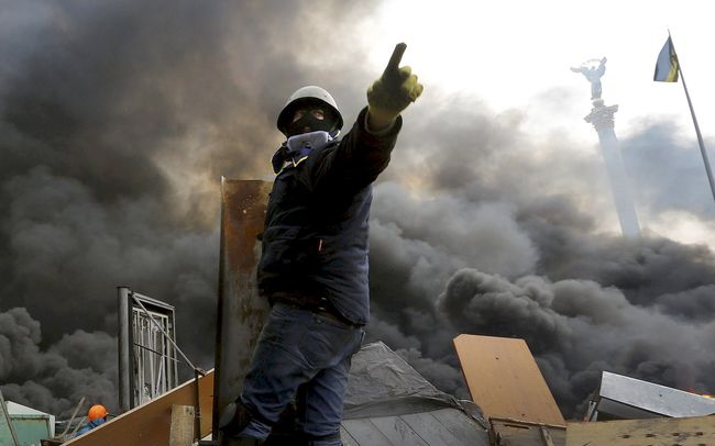An anti-government protester calls upon his comrades to advance over a burning barricade in Kiev's Independence Square